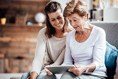 Surprised senior woman using digital tablet by granddaughter at home - p300m2276873 by Gustafsson