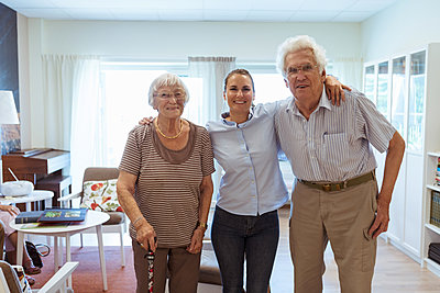Portrait of smiling young woman with grandparents standing together in nursing home - p426m2072583 by Kentaroo Tryman