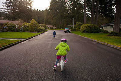 Caucasian children riding bicycles on suburban street - p555m1415208 by Adam Hester