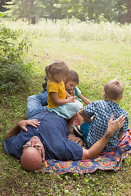 Father and children relaxing on blanket on grass - p924m1224762 by Kinzie Riehm
