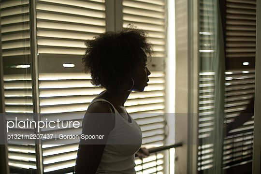 African woman against shutters - p1321m2207437 by Gordon Spooner