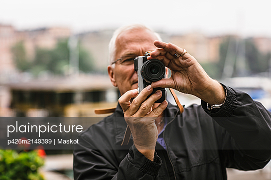 Senior man using camera during photography course - p426m2149399 by Maskot