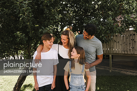 Smiling parents with children against tree in front yard - p426m2238029 by Maskot