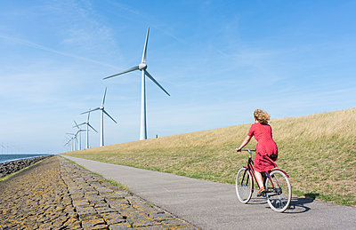 Girl cycling along windfarm - p1132m1591228 by Mischa Keijser