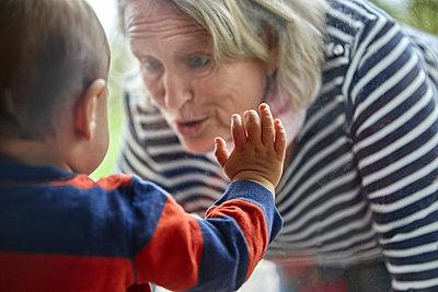 Grandmother meets grandson, portrait - p1146m2187856 by Stephanie Uhlenbrock