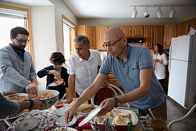 Latinx family enjoying buffet dinner in kitchen - p1192m2034552 by Hero Images