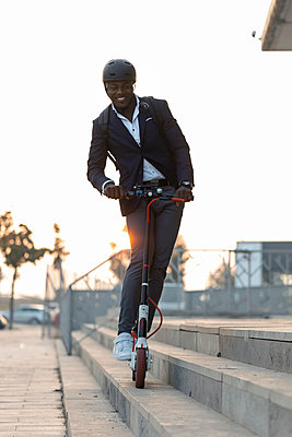 Portrait of businessman with backpack and cycling helmet riding push scooter at sunset - p300m2166563 by Josep Suria
