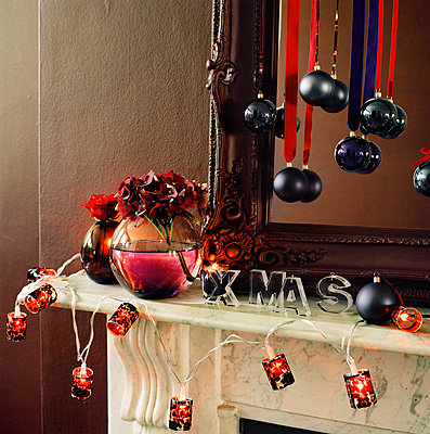 Living room mantelpiece decorated in Christmas decorations and fairy lights - p349m695126 by Emma Lee