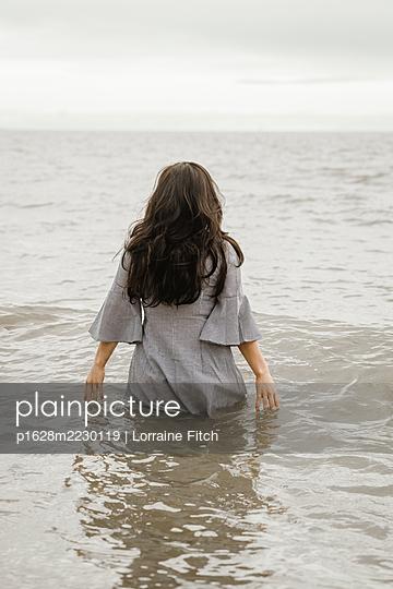Großbritannien, Frau mit langen Haaren und Kleid im Meer - p1628m2230119 von Lorraine Fitch