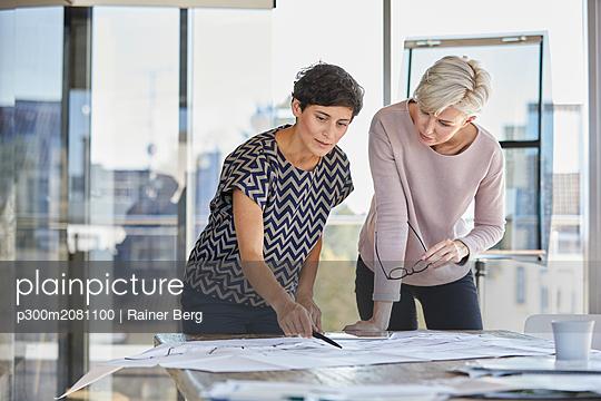 Two businesswomen discussing floor plan on desk in office - p300m2081100 by Rainer Berg