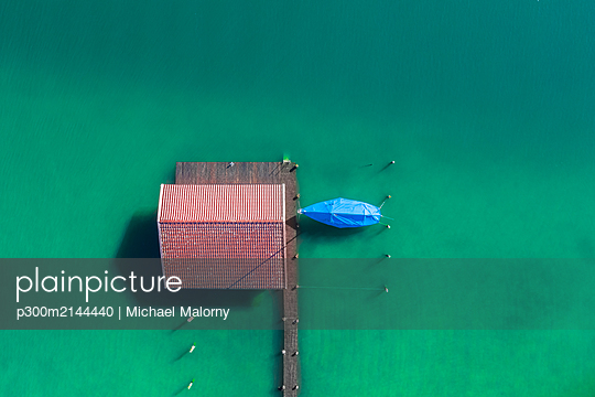 Germany, Bavaria, Aerial view of boathouse standing on green shore of Chiemsee lake - p300m2144440 by Michael Malorny