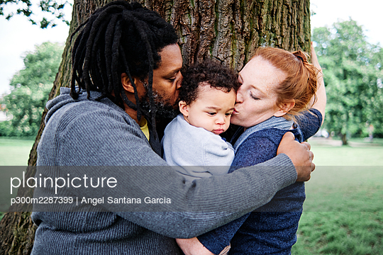 Father and mother kissing son while embracing near tree trunk at park - p300m2287399 by Angel Santana Garcia