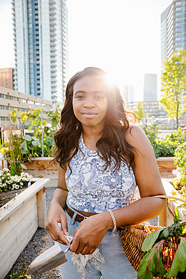 Portrait confident young woman in sunny, urban community garden - p1192m2130344 by Hero Images