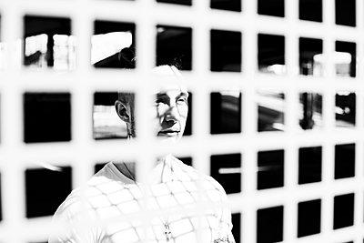 Mann blickt durch ein vergittertes Fenster - p1267m2263376 von Jörg Meier