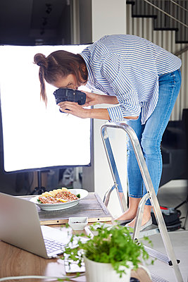 Woman standing on step ladder and photographing food - p300m1537599 by gpointstudio