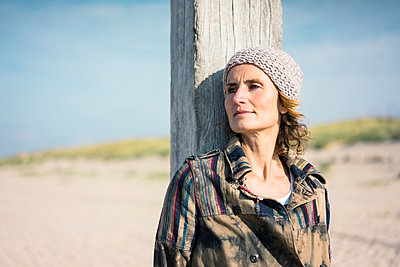 Woman with woolly hat leaning on wood pole - p300m2059305 von Robijn Page