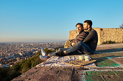 Romantic gay couple sitting on observation point against clear sky, Bunkers del Carmel, Barcelona, Spain - p300m2257348 by Veam