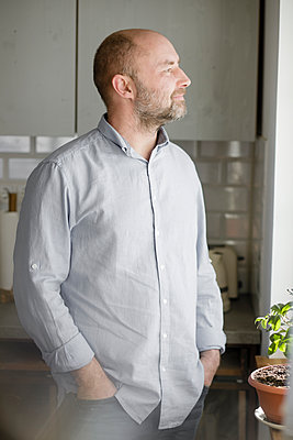 Mature man with hands in pockets looking away while standing in kitchen at home - p300m2266622 by Katharina Mikhrin