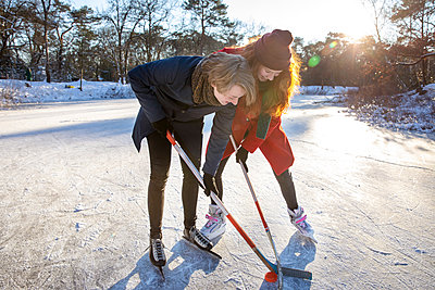 Girlfriend with boyfriend playing ice hockey on frozen lake - p300m2287395 by Frank van Delft