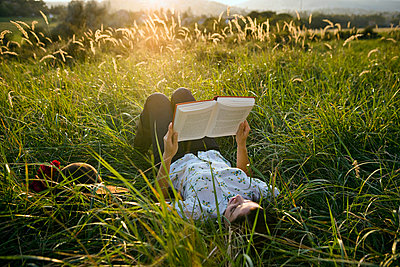 Woman lying in grass reading. - p4291437f by Chev Wilkinson