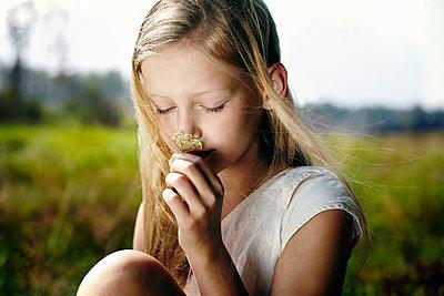 Caucasian girl smelling wildflower in field - p555m1303337 by Vladimir Serov