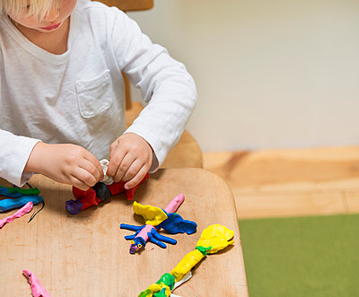 Cropped shot of three year old boy playing with modeling clay - p924m937064f by JLPH
