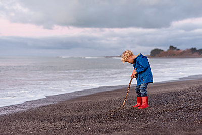 Young boy wearing red boots at beach - p1166m2137164 by Cavan Images