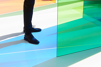 Person in black shoes on colourful floor - p1411m2128329 by Florent Drillon