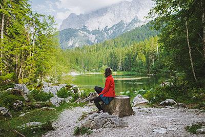 Germany, Bavaria, Eibsee, Woman sitting byÊFrillenseeÊlake - p1427m2174056 by Oleksii Karamanov