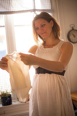 Pregnant woman admiring clothes for newborn baby - p1687m2295128 by Katja Kircher