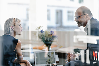 Businessman and woman having a meeting in a coffee shop, discussing work - p300m2140200 by Kniel Synnatzschke