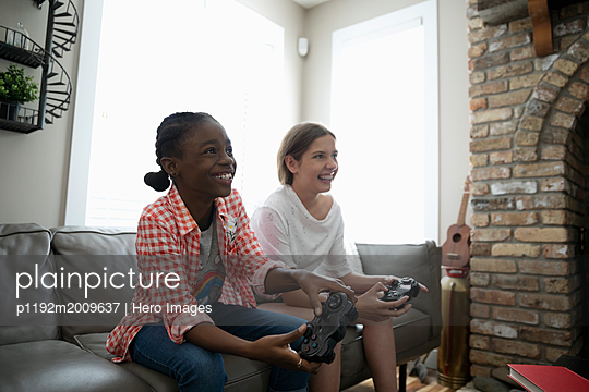 Smiling tween girl friends playing video game on living room sofa - p1192m2009637 by Hero Images