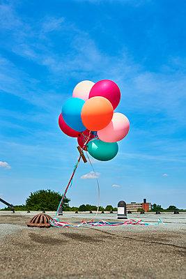 Bunte Ballons auf einem Flachdach - p1076m1582552 von TOBSN