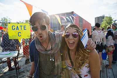 Portrait enthusiastic young couple with summer music festival tickets outside gate - p1192m1173973 by Hero Images
