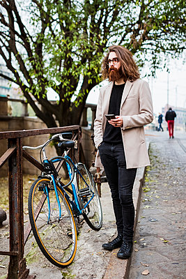 Stylish young man outdoors with cell phone looking around - p300m1204706 by Mauro Grigollo