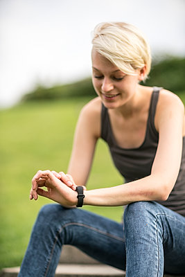 Smiling young woman checking her smartwatch - p300m1206198 by A. Tamboly