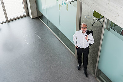 Elevated view of smiling mature businessman standing in office - p300m1563319 by Uwe Umstätter