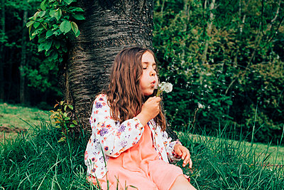 Portrait of girl sitting on a meadow blowing blowball - p300m2102798 von Annie Hall