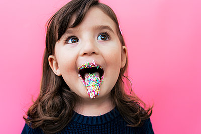 Portrait of happy little girl with sugar granules on lips and tongue in front of  pink background - p300m2170186 by Gemma Ferrando
