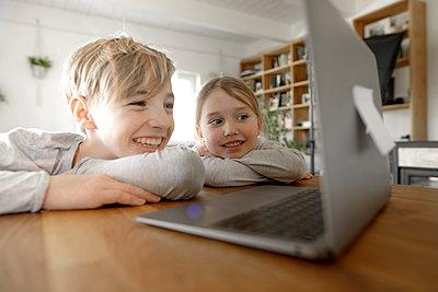 Happy brother and sister looking at laptop together at home - p300m2180911 by Katharina Mikhrin