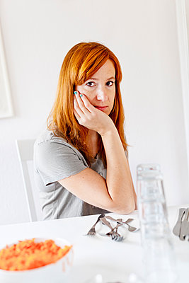 Red haired woman sitting at table - p312m1551974 by Johner Images