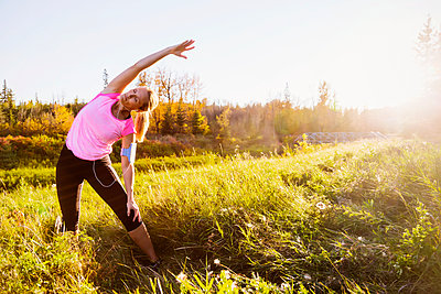 An attractive middle-aged woman wearing active wear and listening to music while pausing to do some stretch exercises during a run in a city park at sunset on a warm autumn evening; Edmonton, Alberta, Canada - p442m2019656 by LJM Photo