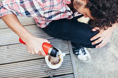 Junger Mann brüht Kaffee auf - p586m1044936 von Kniel Synnatzschke