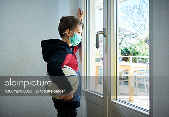 Sad boy with basketball and mask looking out of window - p300m2180353 by Dirk Kittelberger