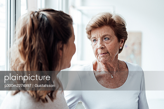 Serious grandmother looking at granddaughter at home - p300m2274997 by Gustafsson