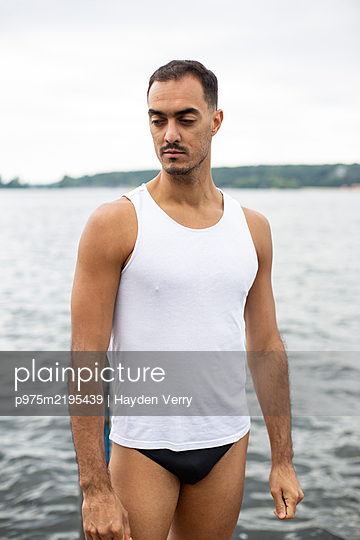 Young man in undershirt on bathing lake - p975m2195439 by Hayden Verry