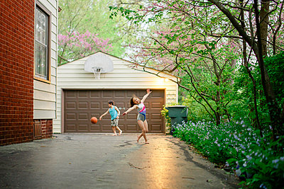 A little girl dances barefoot while brother plays basketball in back - p1166m2157361 by Cavan Images