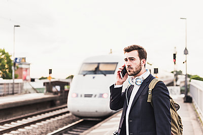 Young man using cell phone on platform as train coming in - p300m1459752 by Uwe Umstätter