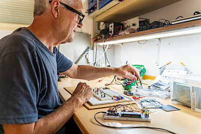 Senior man working on electronic circuits in his workshop - p300m2139835 by VITTA GALLERY