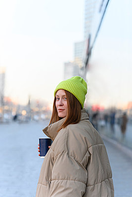 Smiling woman wearing knit hat looking over shoulder while standing on footpath - p300m2282581 by Katharina und Ekaterina